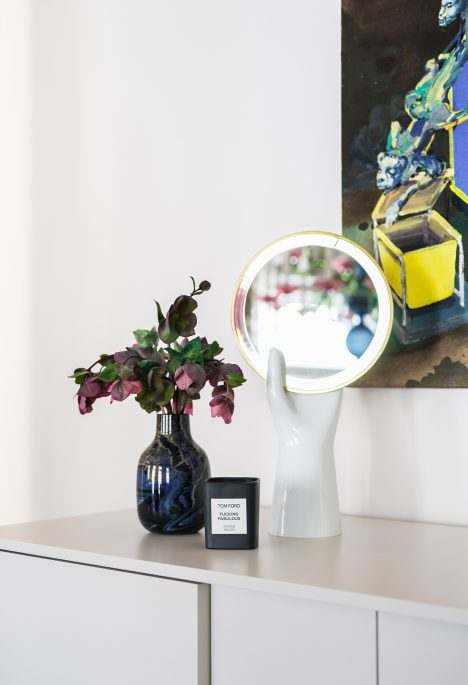 A vase with flowers, design mirror and a candle for home decor