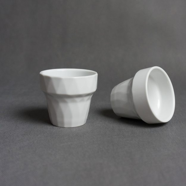 One standing and one laying white cups by Czech designer Filip Mirbauer