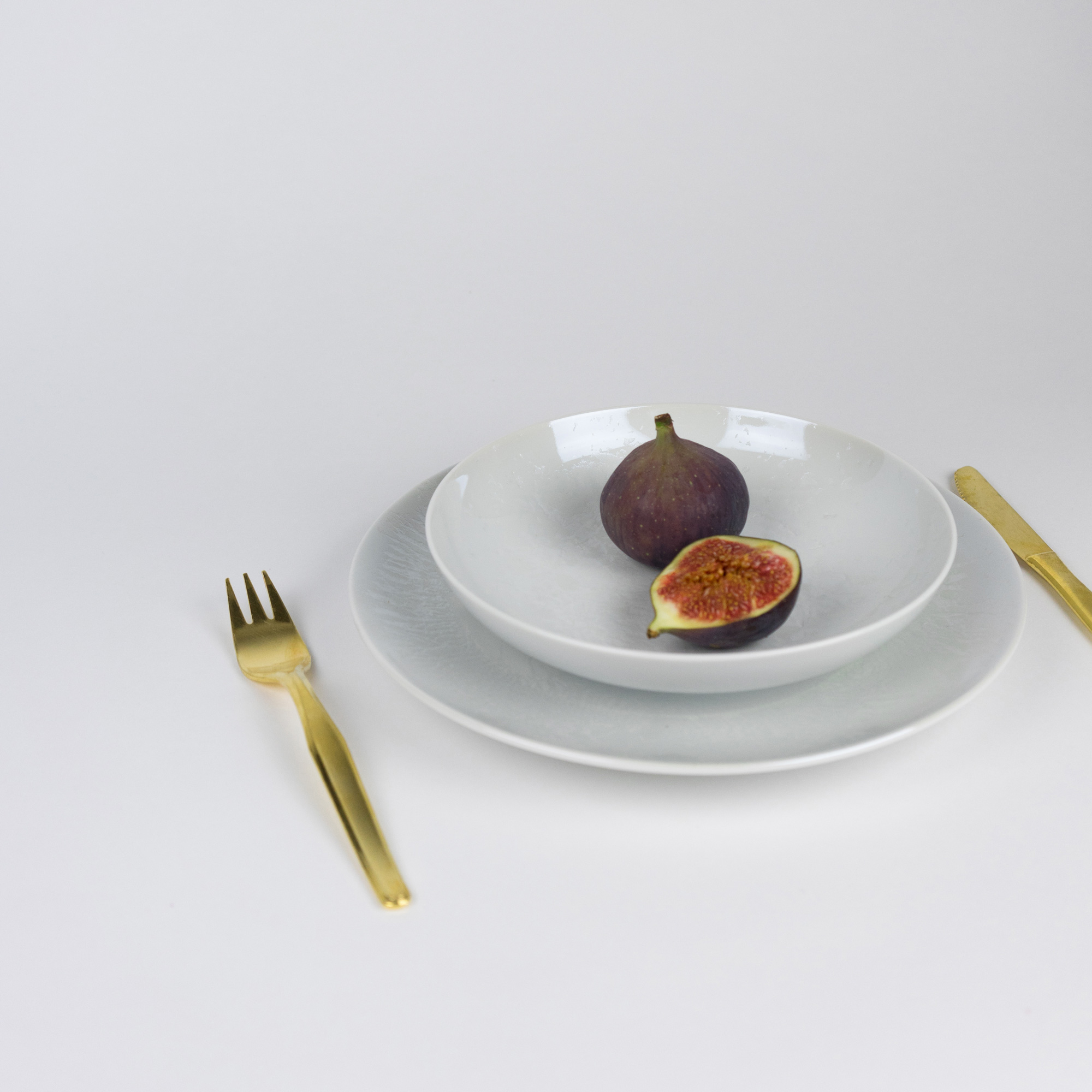 Pearl dinner and soup plates with golden cutlery