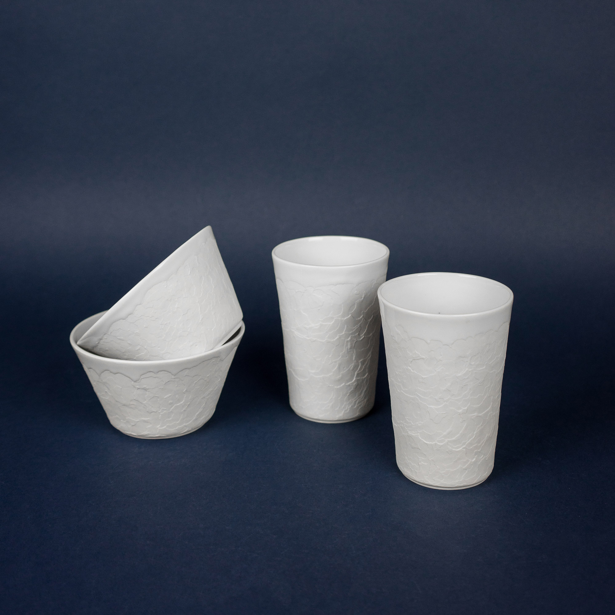 Two white ceramic structure cups and bowls by Czech design studio Nalejto