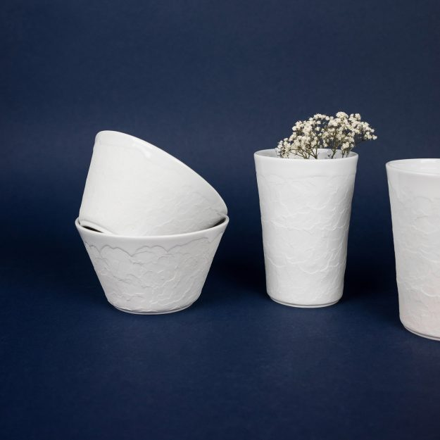Two white ceramic structure cups and bowls by Czech design studio Nalejto with flowers