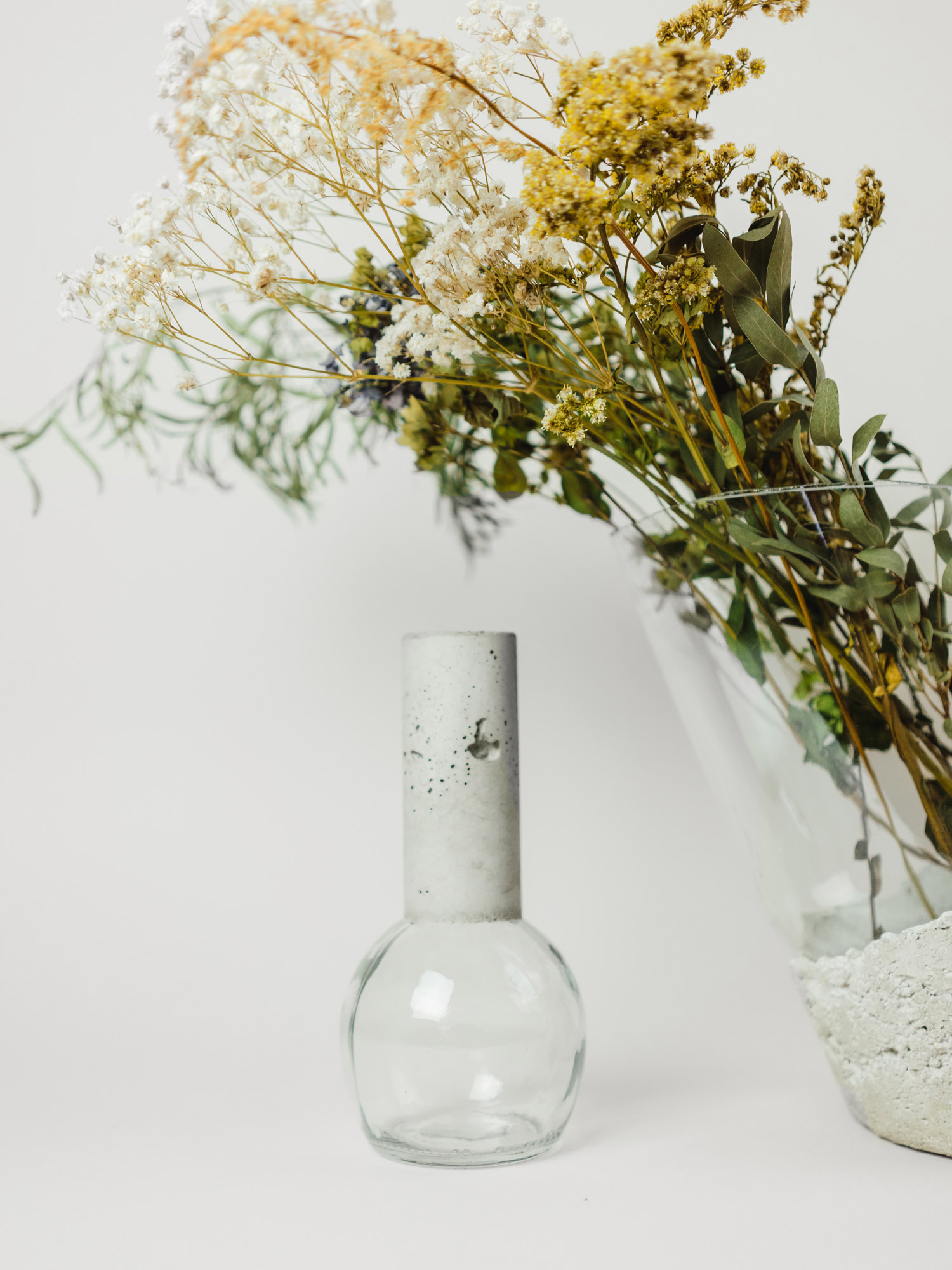 Two concrete and glass vases with flowers by Prasklo
