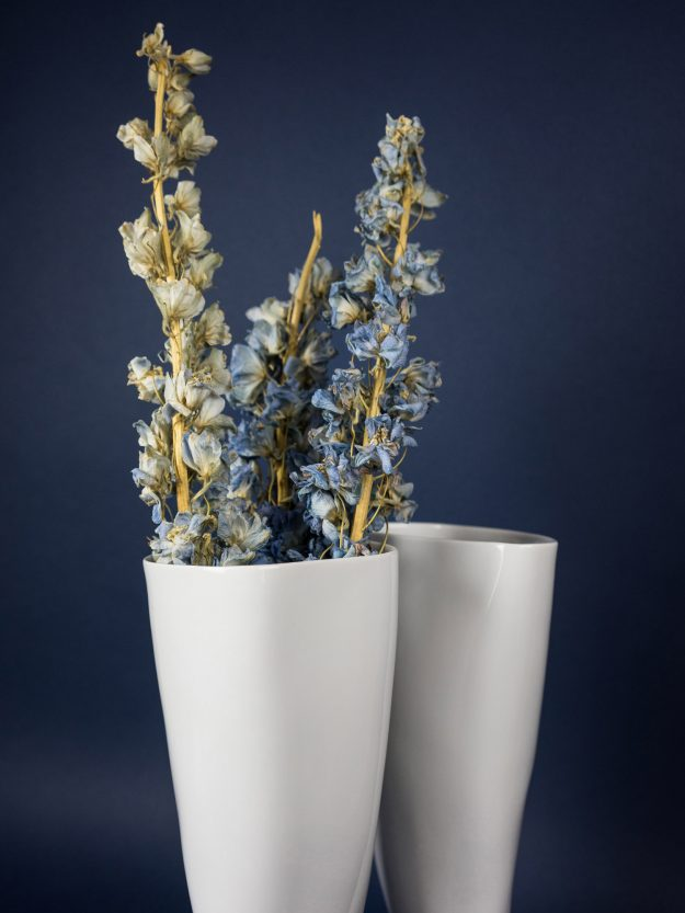Detail of the white boot porcelain vases with dried flower as decor on blue backround