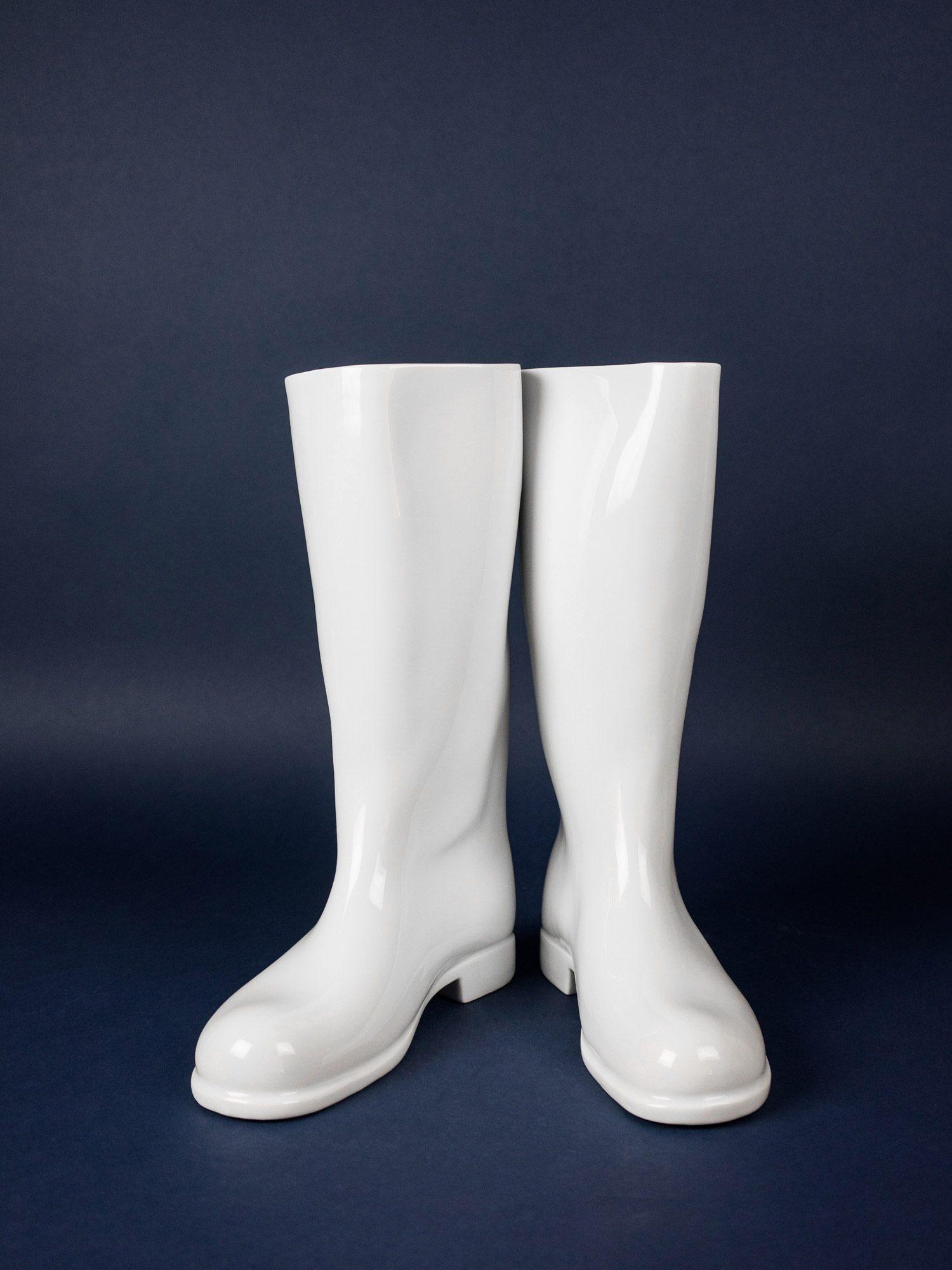 White, porcelain boot vases by Qubus on blue backround.
