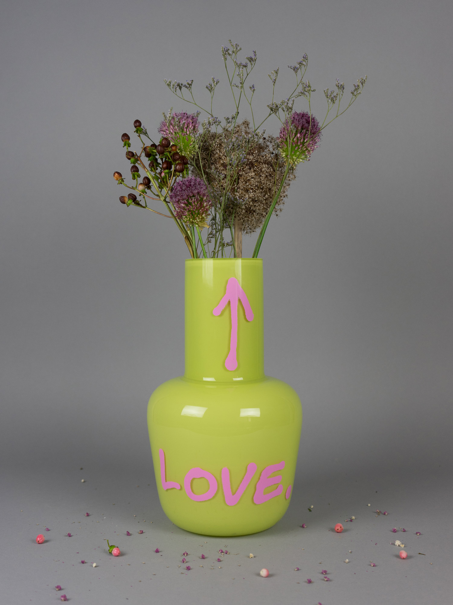 Unnamed neon yellow love vase by Qubus with flowers as decoration