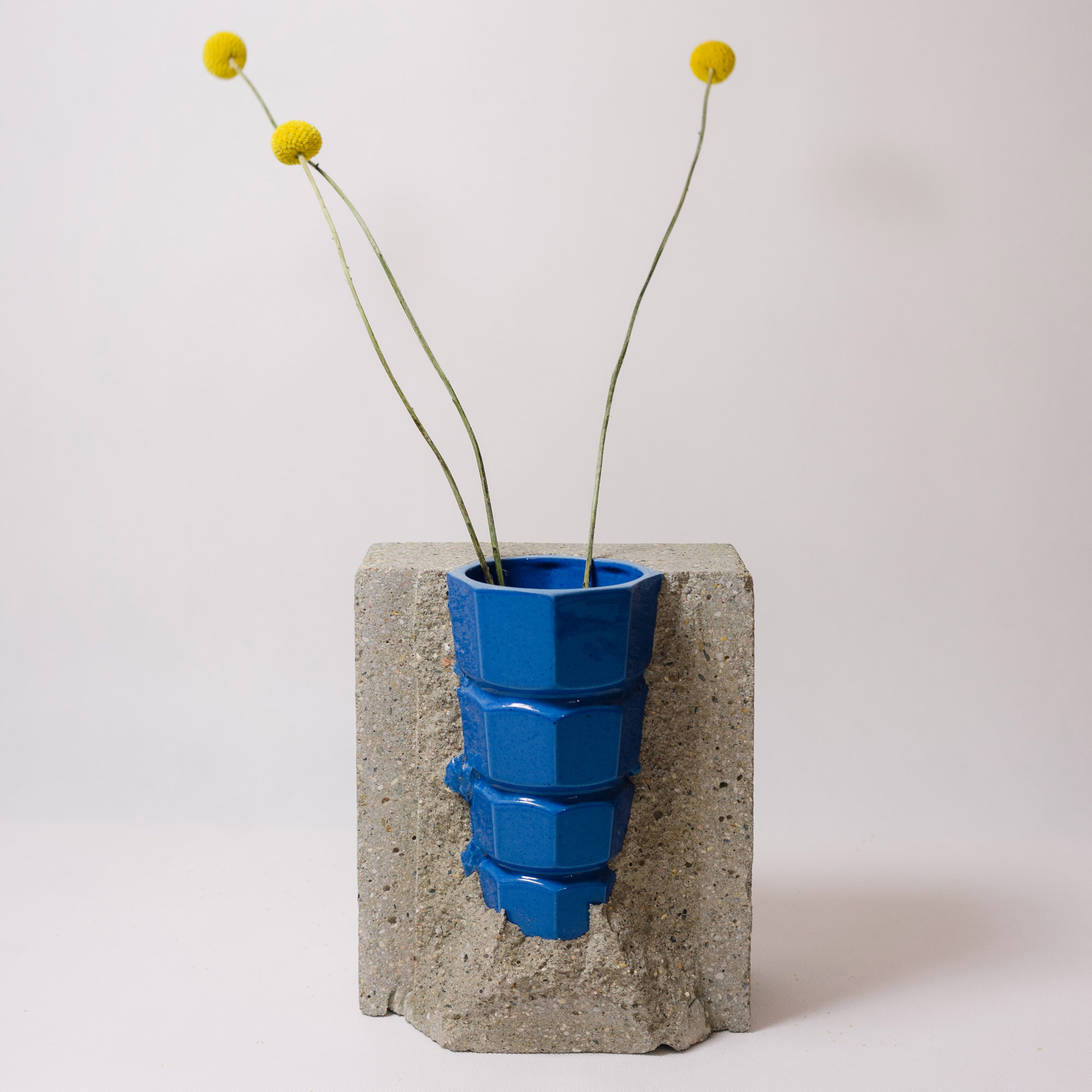 Blue porcelain-concrete vase by Vobouch designers with yellow flowers 01