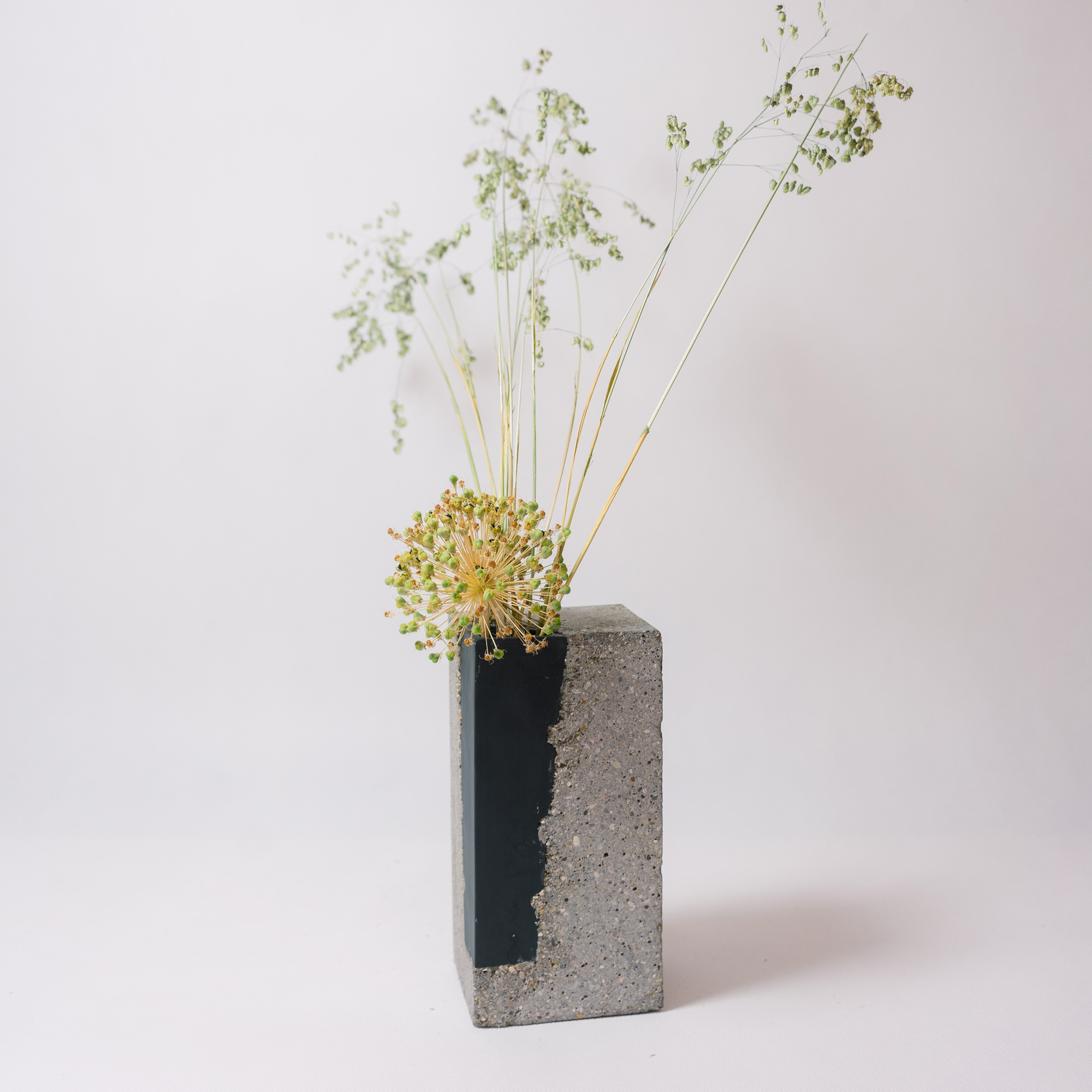 Black coloured porcelain vase encapsulated in concrete by Vobouch designers, with flowers 01