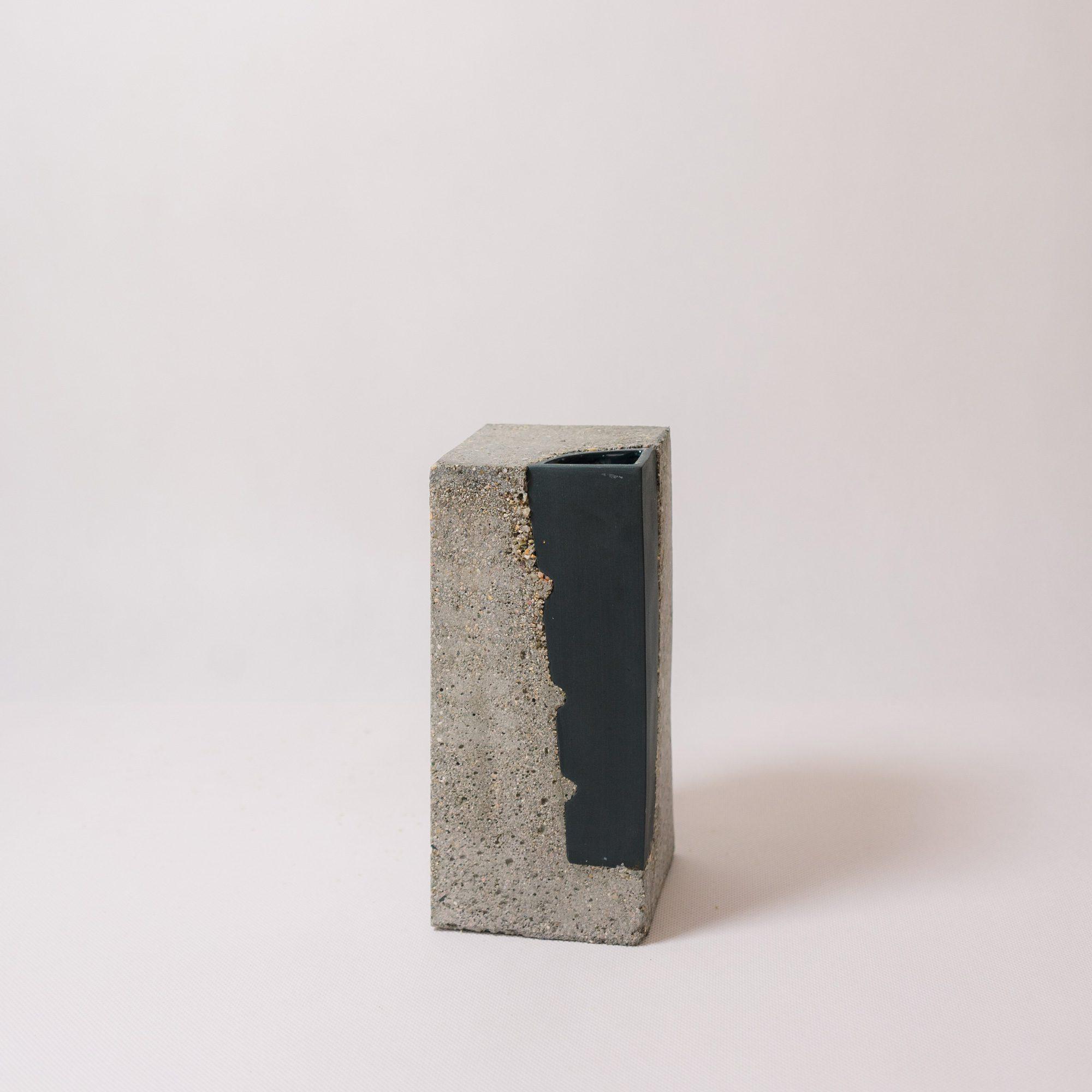 Black coloured porcelain vase encapsulated in concrete by Vobouch designers 02