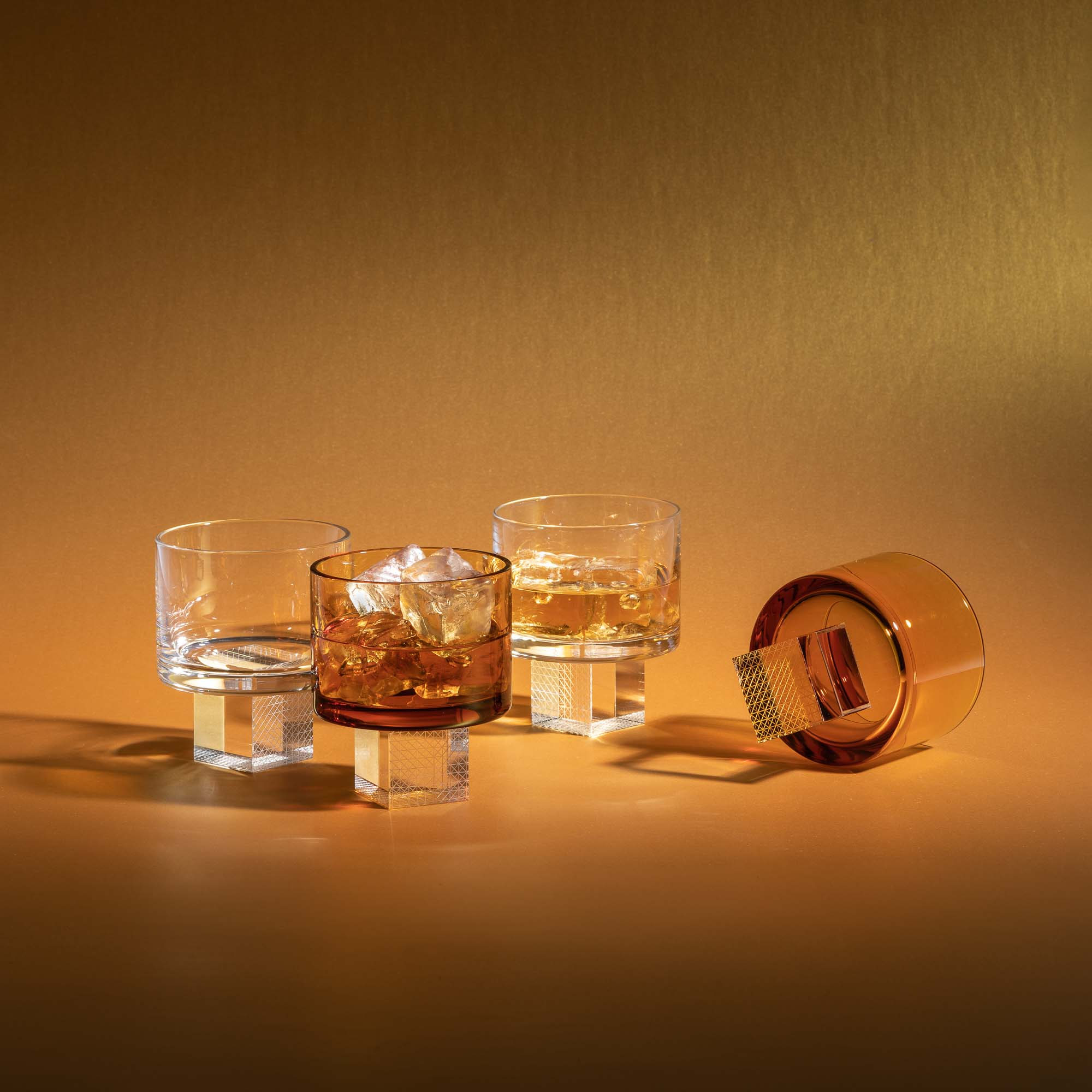 A set of transparent and amber crystal glasses for whiskey by Lukas Houdek