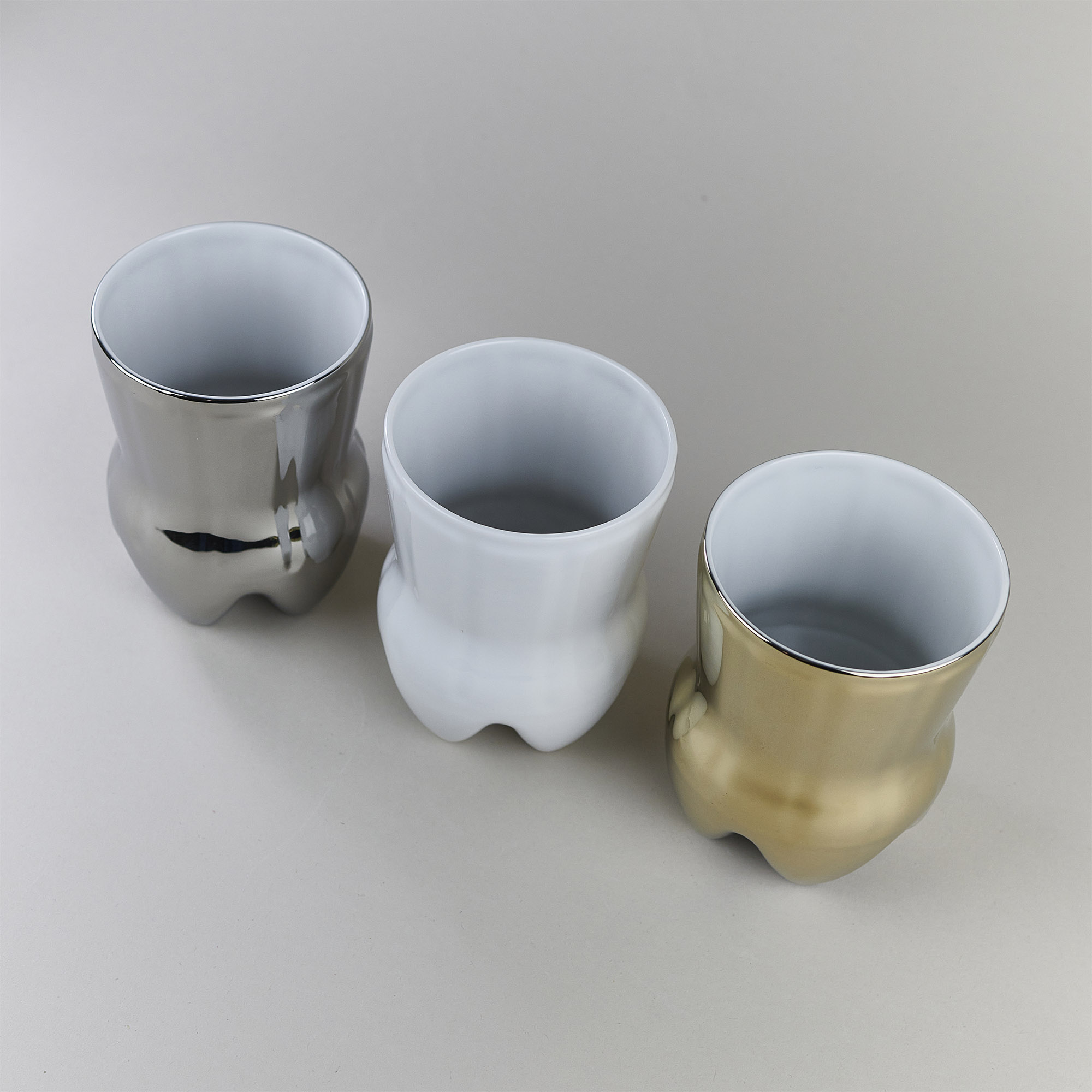 Three porcelain cups in gold, silver and white colours in a shape of Cola bottle by Qubus design studio